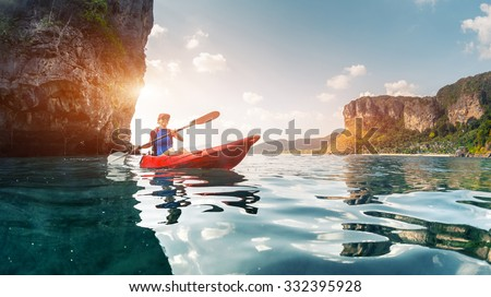 Lady paddling the kayak in the calm tropical bay - stock photo