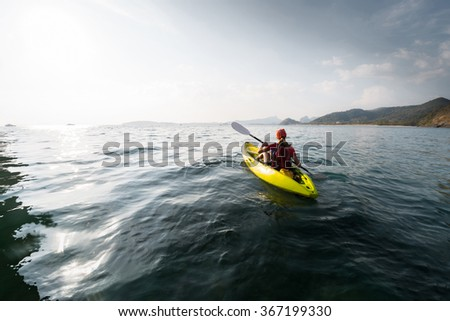 Lady paddling the sea kayak far away from the shore - stock photo