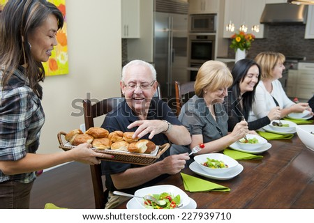 lady passing buns / around the dinner table / at dinner party - stock photo