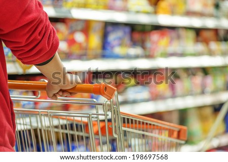 Lady pushing a shopping cart in the supermarket. - stock photo