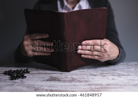 Lady reading bible, wooden table, black rosary