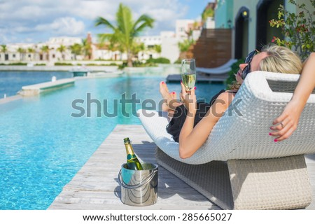 Lady relaxing in deck chair by the pool and drinking champagne