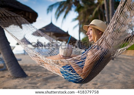 Lady relaxing in the hammock on the sandy beach with view on remote tropical islands. Young blonde woman resting on hammock. Happy woman relaxing on a hammock on holidays