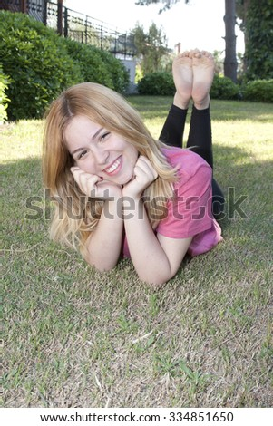 Lady relaxing on the grass - stock photo