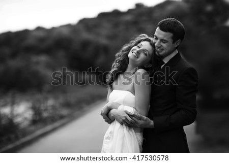 Lady rests on man's shoulder while he hugs her from behind