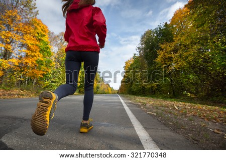 Lady running on the asphalt road through the autumn forest - stock photo