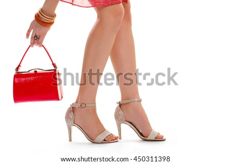 Lady's hand holds red purse. Beige heels and bracelets. Legs of young model. Designer shoes and small accessorries.