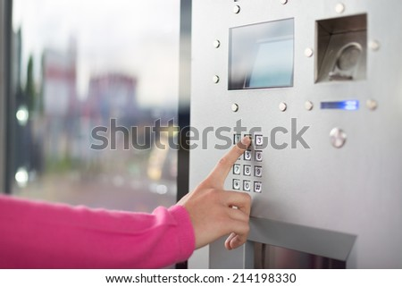 Lady's hand using a dial pad on a vending machine. The fore finger is placed on the dial pad key. - stock photo
