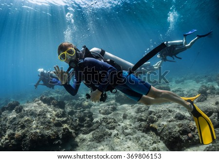 Lady scuba diver showing ok signal underwater