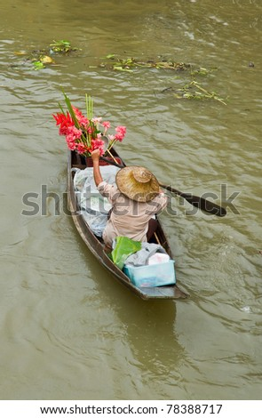 Lady selling flower from her boat at Floating Market, Thailand