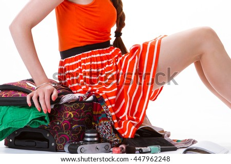 Lady sits on overfilled suitcase. Legs of young woman. Baggage for long trip. She took too many things. - stock photo