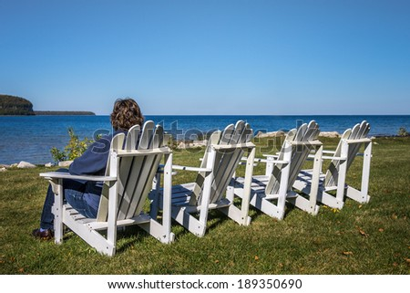Lady sitting in one of four beach chairs in the Autumn looking at the horizon.  Shot in Door County, Wisconsin.  Copy space on top half of frame. - stock photo