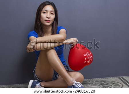 Lady sitting on the floor holding a heart shaped balloon. - stock photo