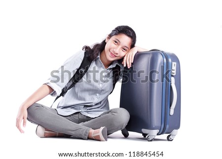 Lady sitting on the floor with a bag and suitcase isolated in white background. - stock photo