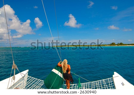 lady stands on a catamaran looking at a distant island - stock photo