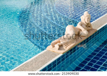 Lady stone carving in blue ceramic swimming pool - stock photo