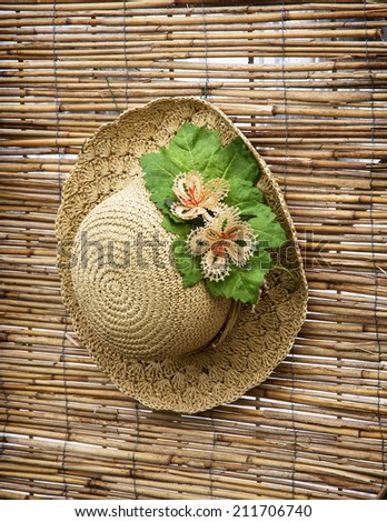 Lady straw hat with decorative flower ribbon hung on the bamboo wall. - stock photo