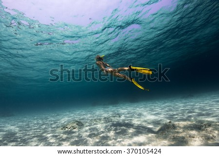 Lady swimming underwater over the sandy bottom in a tropical sea - stock photo