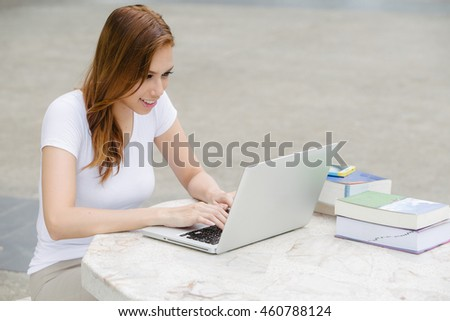 Lady use of laptop on campus.