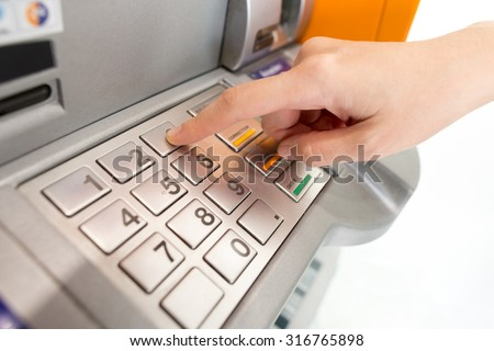 Lady using ATM machine to withdraw her money. - stock photo