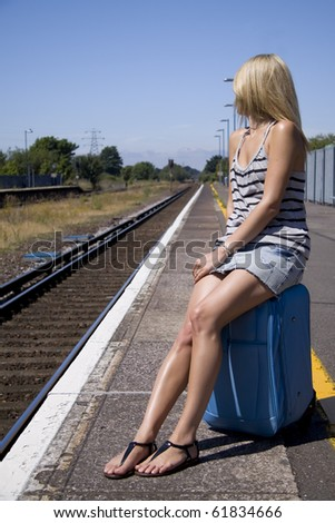 Lady waiting for train sitting on her luggage - stock photo