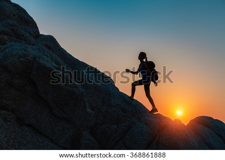 Lady walking on the rocks at sunset