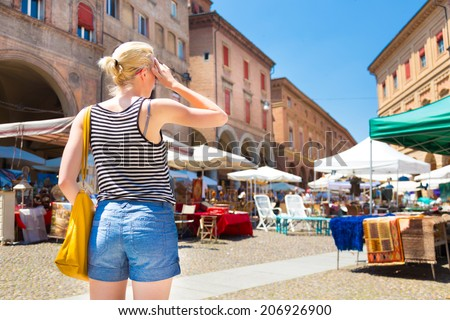 Lady walking the flea market on old traditional Piazza of Santo Stefano square of Bologna, Italy. - stock photo