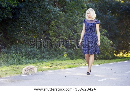 Lady walking with her dog at promenade - stock photo