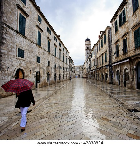 Lady walks through the shiny wet streets at dawn in Dubrovnik - stock photo