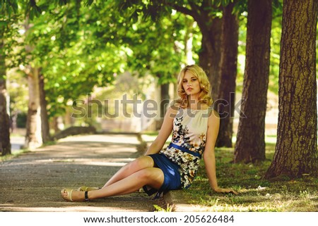 lady wearing dress sitting  in park - stock photo