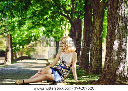 lady wearing dress sitting in the park - stock photo
