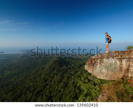 Lady with backpack standing by an edge of a cliff and enjoying valley view - stock photo