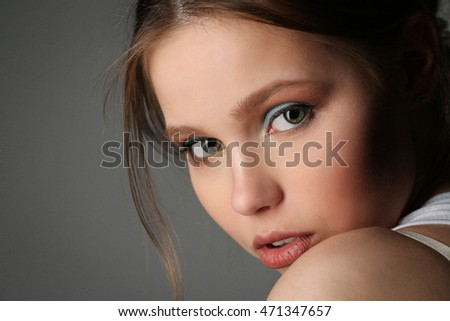 Lady with big eyes looking into the camera. Close up. Gray background