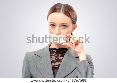Lady with business card. Confident young woman holding business card in front of her mouth card in her hand and while standing isolated studio background - stock photo