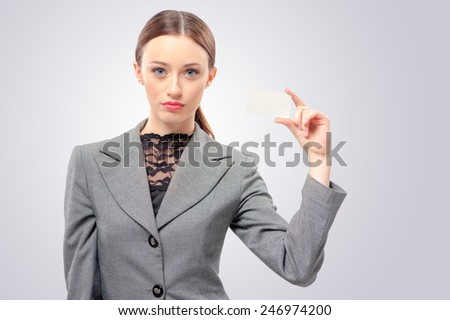 Lady with business card. Confident young woman holding business card in her hand and while standing isolated on white - stock photo