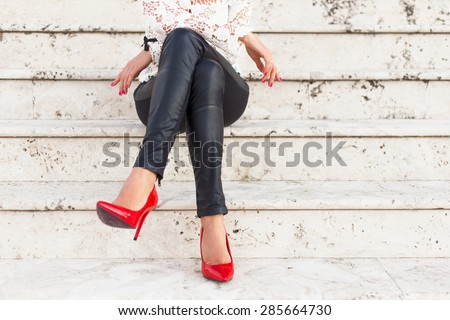 Lady with red high heel shoes sitting on stairs - stock photo