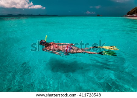 Lady with snorkel and fins swims near the shore - stock photo