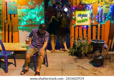 LAEM CHABANG, THAILAND, DECEMBER 26:A drunk and tired man is sitting in front of a traditional Thai Karaoke wooden house in the city of Laem Chabang, Thailand. - stock photo