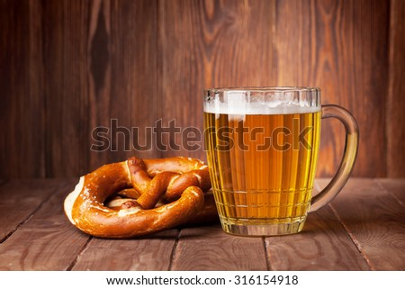 Lager beer glass and pretzel on wooden table. View with copy space - stock photo