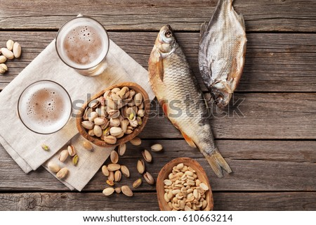 Lager beer glasses and snacks on wooden table. Nuts, chips, dry fish. Top view