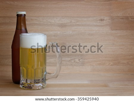 Lager beer in glass and bottle over wood