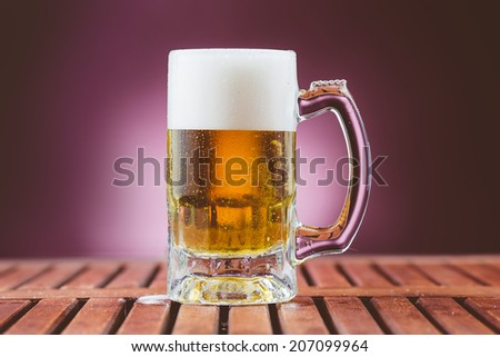 Lager beer in mug with foam and bubbles on wood table