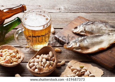 Lager beer mug and snacks on wooden table. Nuts and dry fish