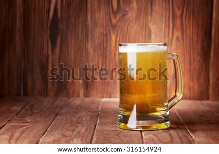 Lager beer mug on wooden table. View with copy space - stock photo