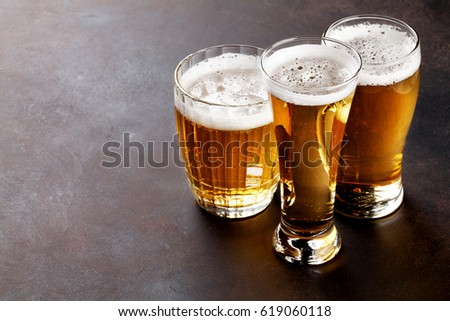 Lager beer mugs on stone table. With copy space