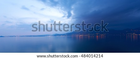 Lago di Garda at night (Garda Lake), the largest Italian lake of glacial origin with the lights of the coast of Lombardy, Italy