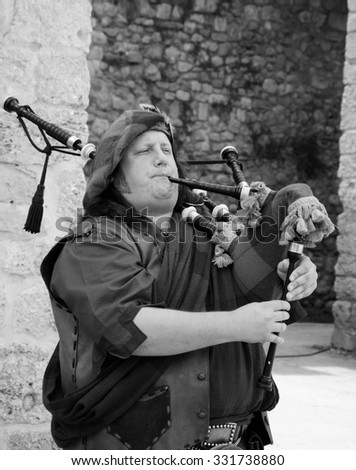LAGOS, PORTUGAL - MAY 3, 2015: Bagpiper in traditional costume playing at local medieval fair. - stock photo