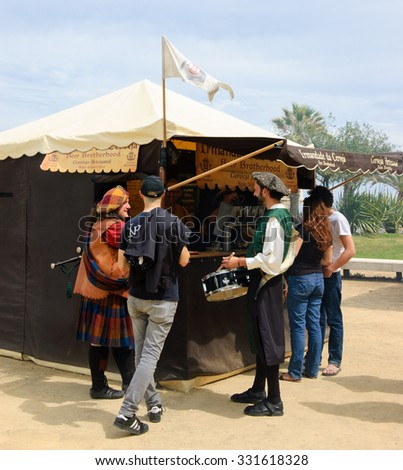 LAGOS, PORTUGAL - MAY 3, 2015: Musicians in medieval costumes and other customers buying beer at boutique brewery stall during local medieval fair. - stock photo