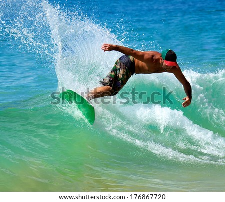 LAHAINA, HAWAII - CIRCA OCTOBER 2013: A man skimboarding at Big Beach in Maui Hawaii. Skimboarding originated in Southern California when lifeguards wanted an easy way to get across Laguna beaches.
