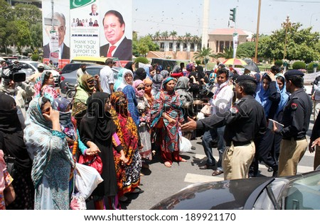 LAHORE, PAKISTAN - APR 29: Teachers employees of (ETPB) chant slogans against non-regularization on their jobs and non-issues of their dues salaries during protest on April 29, 2014 in Lahore.